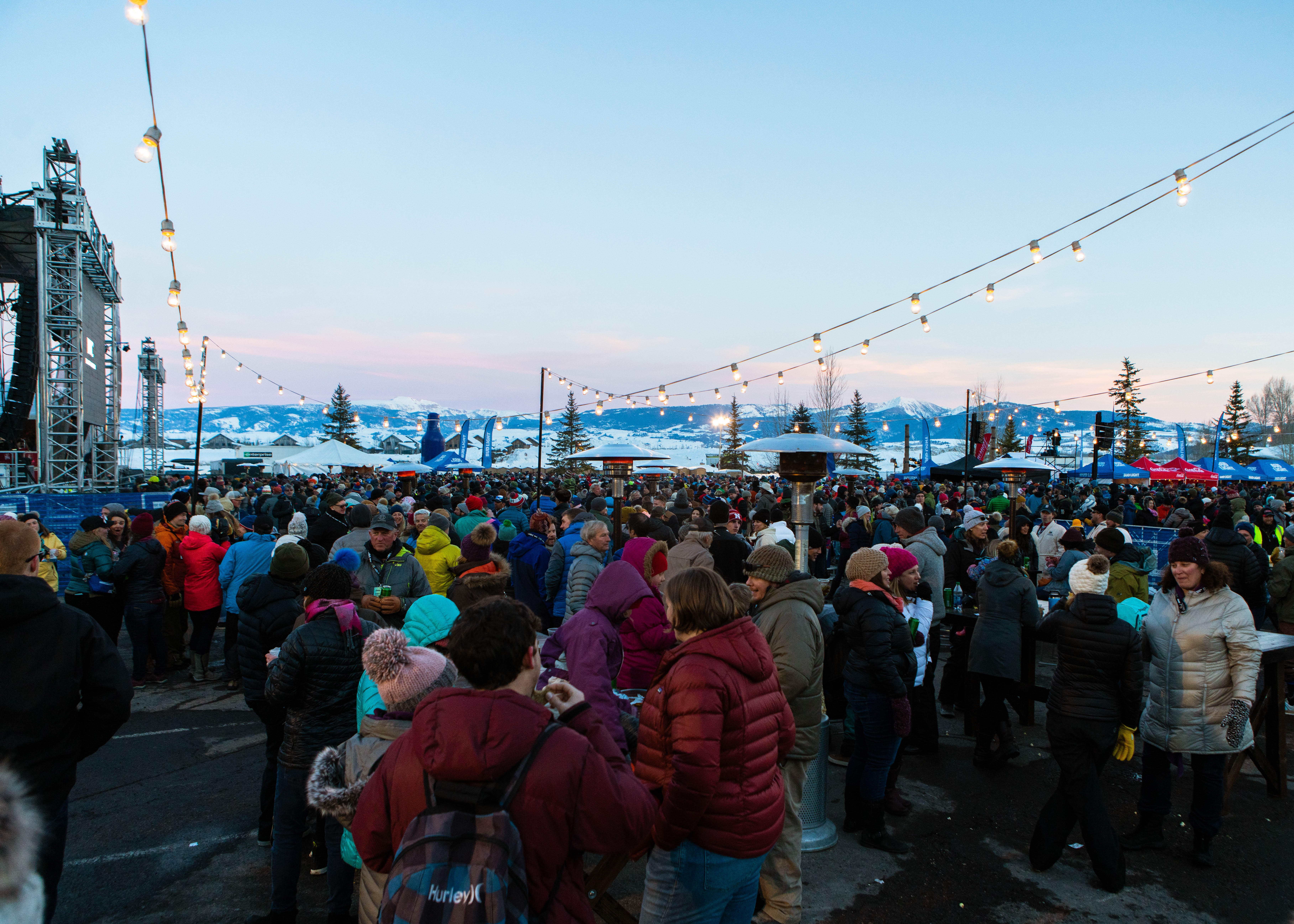 Festival goers at Rendezvous Festival mingle alongside the stage. Overlooking beautiful mountain views.